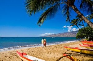 "Maui ""The Magic Isle"" - Couple walking along the beach with canoes in the foreground"